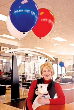 "Susie Everett holds Beau, a schnauzer who comes to work with her every day, in the showroom at Everett Buick GMC. Everett is known as the ""face"" of the family-owned dealership."