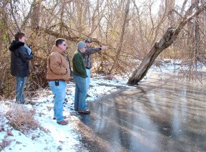Ron Moore, Arkansas Game and Fish Commission biologist (right), along with AGFC biologist John Stein, explains to Gentry Chamber of Commerce director Bev Saunders and city councilman Jason Barrett problem issues with two beaver ponds on city-owned property which would likely need to be resolved if the ponds are to be stocked and used for public fishing.
