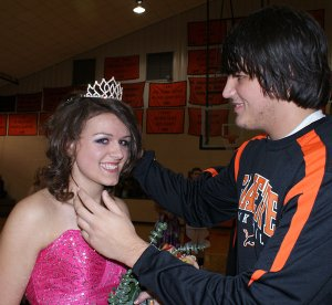 Gravette Lion Cody Montee adjusts the crown for Homecoming Queen Samantha Van Otterloo after she was presented her traditional bouquet by her other escort, Matthew Van Otterloo.