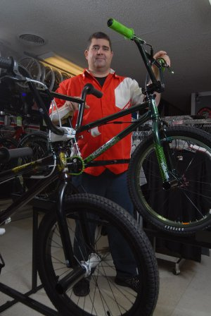 Shawn Basinger shows off some of the BMX bikes at Basinger Bikes in Cabot.