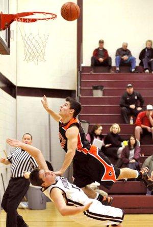 Darrick Strzelecki, of Gravette, knocks Gentry's Kevin Scherer off his feet during play under the basket last week.