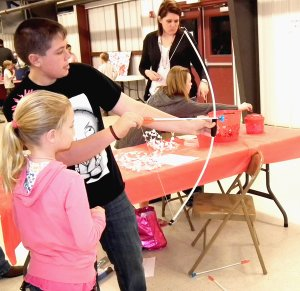Jackson Stickles helped Megan McCullom with her archery at the Benton County 4-H Valentine Carnival on Feb. 19.