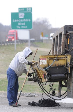 Tim Fosdick, with the Bella Vista Property Owners Association's Street Department, drops asphalt into a pothole Wednesday in Bella Vista. The association could be fined by the Arkansas Contractors Licensing Board for performing contract work without a license.