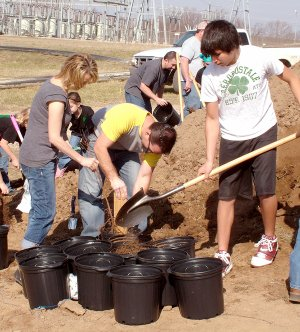 Gentry mayor Kevin Johnston (center), with his wife Lori and Dakota Smith, help plant trees.