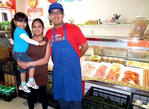 Daniel Ortiz, manager and butcher of the Carniceria Guanajuato Meat Market in Decatur, stood in front of the store's meat case with his wife Marina and daughter Nelly.
