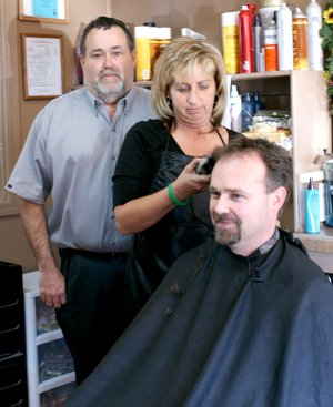 Zane Vanderpool, principal at Glenn Duffy Elementary School in Gravette, is ready as Michelle House at The Patio in Gravette readies her clippers.