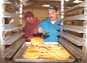 Lions Club member Mark Burden tosses pancakes from the griddle onto the serving pan during the annual pancake supper on Thursday in Gentry. Terrell Shields is frying pancakes in the background. Proceeds raised by the club are used to pay for eye glasses and eye procedures for those who cannot afford them.