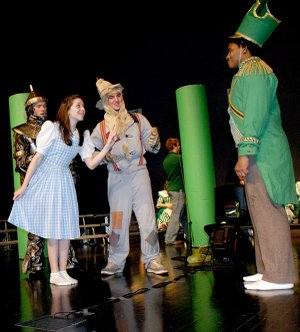 "Dorothy (Rachael Morris), Tinman (Adam Smith), and Scarecrow (David Carnahan) are confronted by Guard (Kahlief Steele) in the ""Wizard of Oz"" production. Photos by Dodie Evans"