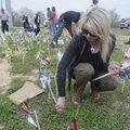 RAISING AWARENESS Heather Spradlin of Bentonville helps install pinwheels Thursday in front of the B...