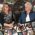 "Quilters Karen Kielmeyer and Margie Langanke chat in front of Langanke's ""Barns for Every Season."" T..."