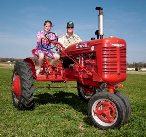 "Madison Bunch, 10, with her grandfather, Glenn Smith, drive a 1945 B Farmall tractor on the grounds of Tired Iron of the Ozarks, in Gentry, in preparation for the annual spring show this weekend. The tractor, outfitted by Smith with two seats, and a clutch and brake pedal on each side, is the club's new ""driver's ed tractor."" Rides will be offered without charge to children, 8 and above, this weekend."