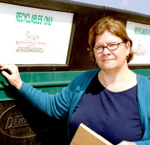 Allyson Ransom at the recycling trailer with bins that are plainly marked with the items that are acceptable in each particular bin. An open-top cardboard trailer is parked nearby. The service is available adjacent the Gravette Police Department.