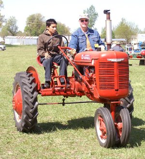 "Lane Dannels, 12, takes a drive around the Tired Iron showgrounds on the club's new ""driver's ed tractor"" with Glenn Smith."