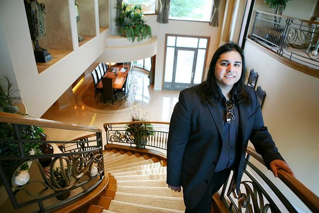 zar-zanganeh-a-realtor-with-luxe-estates-collection-stands-for-a-photograph-in-the-foyer-of-a-luxury-home-previously-owned-by-actor-nicolas-cage-in-las-vegas-nevada-us-on-wednesday-april-20-2011-a-growing-number-of-high-end-homes-are-selling-at-a-loss-or-facing-repossession-by-lenders-in-las-vegas-which-already-has-the-highest-rate-of-foreclosure-filings-among-large-us-cities-photographer-ronda-churchillbloomberg-zar-zanganeh