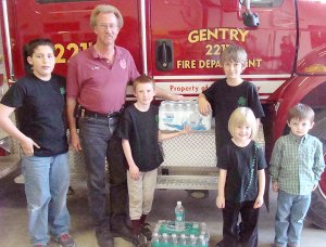 Matthew Nance (left), Fire Chief Vester Cripps, Ben Philpott, Wyatt Philpott, Kayla Philpott and Houston Nance pose for a photo when the Outdoor Adventures 4-H club donated bottled water to the Gentry Fire Department.