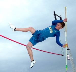 Decatur student Evan Owens pushes to get over the bar during pole vaulting competition at the Gravette Lion Invitational track meet on Monday.