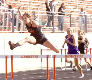 Hurdling to a first-place finish  — Gravette senior Taylor Kean clears a hurdle and is well ahead of her competitors in the 100-meter hurdles at the district track meet in Gravette on Thursday. She finished the event more than a second ahead of the second-place runner, with a time of 16.94.
