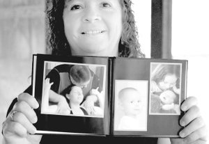 Joy Coonfield shows photos of children and families she helped in childbirthing.