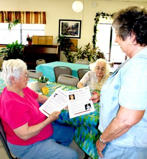 "Mary Kay Kelley, right, director of the Billy V. Hall Senior Activity Center in Gravette shares copies of ""Brain Aerobics Weekly"" with Estelle Marney and Shirley Ball at the Center."
