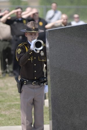 Matt Van Winkle, a member of the Arkansas Sheriffs' Association Honor Guard, participates Monday in the unveiling of the Fallen Officer Memorial at the White County Law Enforcement Center in Searcy.