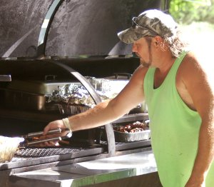 Tim Richardson barbecues chicken in the park for those attending the annual Springtown event on Saturday.