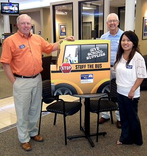 Jerry Cavness, area United Way coordinator, placed a stuff the bus collection box in the lobby of the Arvest Bank in Gravette. Pictured on the left is bank president Jim Singleton and on the right is financial services representative Mai Kia Vang-Thao. United Way is collecting school supplies for students in need in Gravette and Decatur. Arvest Bank is one of many collection sites.