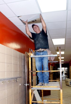 Larry Weihe installs a ceiling tile panel in the hallway at Glenn Duffy Elementary School in Gravette.