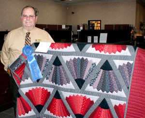 Kiwanis club member Rickie Stark with the prize winning quilt the club will give away on Gravette Day.