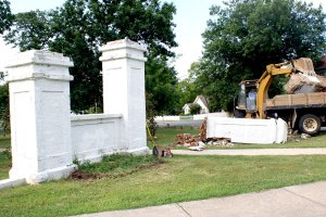 A backhoe loads a huge chunk that was part of one of the entrance pillars at Captain Field Kindley Park in Gravette. The pillars are in the process of being replaced.