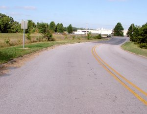 Trucks using this Arkansas Highway 59 spur sometimes are blocked by a train parked on the tracks and back out onto the main highway. Being discussed is the purchase of land to the left of the spur for a truck turnaround.