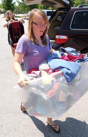Volunteers Rebekah Egle, right, and Hannah Johnson carry in clothing donated Tuesday for the First Baptist Church of Bentonville's clothing giveaway. The giveaway for men, women and children clothing will be at the church, 200 S.W. A St., from 7 a.m. to 11 a.m. Saturday.