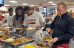 University of Arkansas football players (left to right)  Jacoby Walker, Keante Minor, Alonzo Highsmith and Coach Bobby Petrino fill up their plates during a team dinner Wednesday evening at Razorback Stadium in Fayetteville.