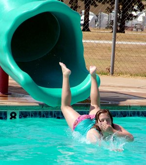 Nikki Lester hits the water after coming off the slide at the McKee Foods pool Saturday. Those who took part in the summer reading program at Gentry Public pool Library enjoyed a pool party, inflatable rides and hot dogs.