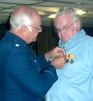 Lt. Col Gray pinned service medals on Gravette resident John Roquemore at a July 9 ceremony.