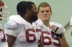 University of Arkansas offensive linemen Alvin Bailey (left) and Mitch Smothers get ready to run drills during practice at the University of Arkansas.