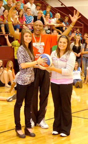 "Gentry High School students Suzie Sikes and Kendra Pettit are pictured with Harlem Swish Captain ""Magic"" Valentino Willis at an anti-drug school assembly on Aug. 24. Willis encouraged students to respect parents and teachers and to refuse alcohol and drugs."