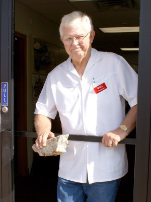 Gravette pharmacist, Ron Teasley, looks out through the frame of what was the back door to Teasley Pharmacy which was burglarized early last Wednesday. Teasley is holding a large concrete/stone, similar to the one used to smash the glass in the store door.
