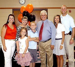 Mitchell Wilber, center, surrounded by family, including his wife Jane on his right, was honored upon his retirement from the Gravette Public School system. Others, from the left, are his daughter, Cory Wilber; grandchildren, Henley and Rayner; and his daughter Camron and her husband Phil Whitehead.