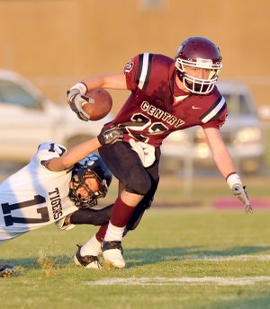 Charleston defender Seth McCann tries to drag down Gentry running back Jarod Cousins in the first half of Friday night's game in Gentry.
