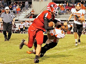 Gravette's Adam Roberts gets face masked by a Poteau ball carrier during Friday night play in Oklahoma. Sam Riester, 35, heads for the action.