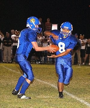 Decatur quarterback Evan Owens handed the ball off to running back Joe Castaneda during Friday's game against the Hackett Hornets.