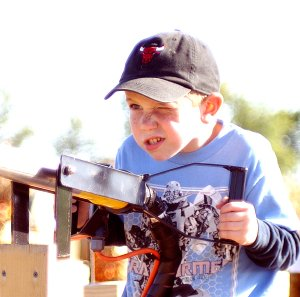 Taking Careful Aim — Jamie Holt, 7, of Gentry, takes aim at downfield targets with an air cannon at the Bloomfield Corn Maze on Sunday. Holt, with his mom and siblings, enjoyed the afternoon, going through the hay maze, riding on a horse-drawn wagon and participating in other games and activities. For more photographs and information on the maze, see Page 8B.