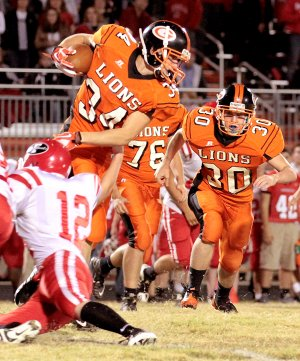 Photo by Heather Brody Gravette senior Dallas Kerley, assisted by junior Brenton Ogle, attempts to pick up yards for Gravette in play against Farmington on Friday.