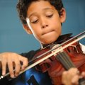 MUSIC MAN Eli Conley, 9, concentrates Tuesday while learning to play the violin during an after-scho...
