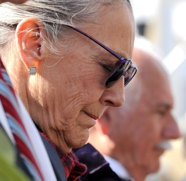 Photo by David Frank Dempsey—                                                                                        Alice Walton and architect Moshe Safdie bow their heads during a Veterans Day ceremony before opening festivities for the museum.