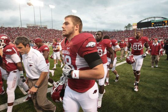 Arkansas tight end Garrett Uekman runs on the field with team mates Saturday, Nov. 19, at War Memorial Stadium in Little Rock.
