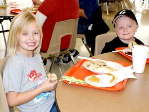 Paige Greer and her brother Peyton enjoyed the Gravette Community Thanksgiving dinner Saturday at the Gravette High School Commons. The children of Mr. and Mrs. Josh Greer, along with their friend Trinity Burnett, were credited with saving the life of an elderly lady who had fallen in her yard near Decatur.