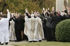 Mourners and clergy raise their hands as they call the Hogs, the University of Arkansas Razorback cheer, after the funeral of tight end Garrett Uekman at Christ the King Catholic Church in Little Rock, Ark., Monday, Nov. 28, 2011. Uekman died Nov. 20 from an undiagnosed heart condition. He was 19. (AP Photo/Danny Johnston)