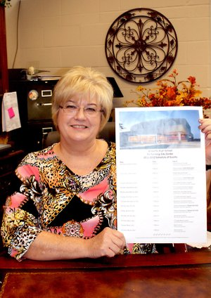 Gravette High School Principal Jo Ellen Hastings holds a poster that lists upcoming programs at the high school performing arts center during the coming months. The attractive posters are posted throughout the community and consulting the list below will enable persons to plan attendance at the events.