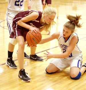 Lauren Little of Gentry struggles to retain possession of the ball against a Rogers player on Nov. 29 in the Benton County Junior High Tournament held at Gentry.